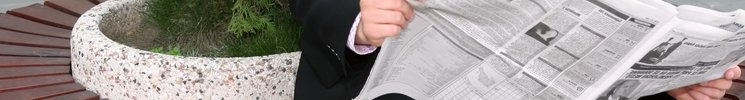 Image of business man sitting on a bench and reading newspaper.
